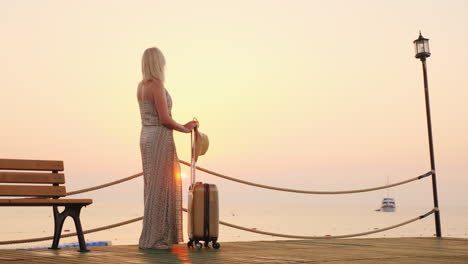 A-Young-Girl-In-A-Summer-Sundress-Expects-To-Settle-In-A-Resort-Hotel-Stands-With-A-Suitcase-On-The-