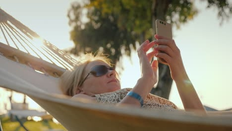 A-Woman-Uses-A-Smartphone-On-Vacation-Relaxes-In-A-Hammock-In-The-Early-Morning-4k-Video