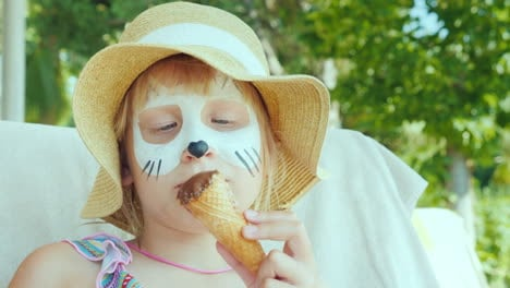 A-Girl-With-Aquagrim-On-Her-Face-Eats-Ice-Cream-In-The-Resort-With-A-Child-Concept