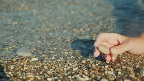 A-Woman-s-Hand-Holds-A-Pebble-Against-The-Background-Of-The-Surf-4k-Video