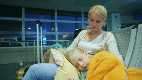 A-Woman-Is-Stroking-A-Girl-Sleeping-On-Her-Lap-Sitting-In-The-Terminal-Of-The-Airport-Flight-Delay-C