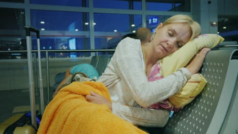 The-Tired-Woman-Sleeps-In-The-Terminal-Of-The-Airport-Cancellation-Or-Delay-Of-The-Flight-Concept
