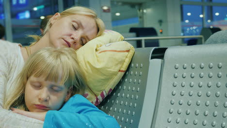 Tired-Woman-With-A-Child-Sleep-In-The-Airport-Terminal-Delay-Or-Cancellation-Of-Voyage-Concept
