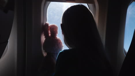 The-Child-Together-With-The-Toy-Hare-Looks-Through-The-Airplane-Window-Vacation-With-A-Child-And-Tra