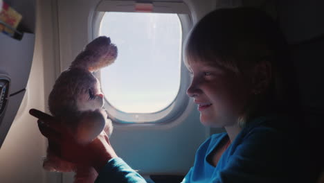 The-Girl-Is-Traveling-On-A-Plane-With-Her-Favorite-Toy-Happy-Childhood-And-Vacation-With-The-Baby-Co