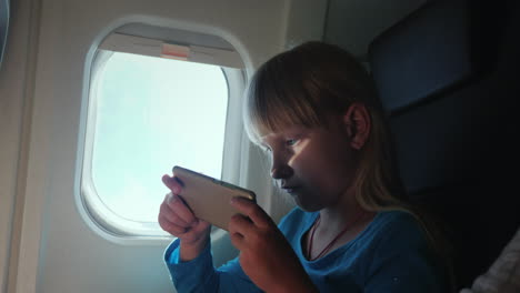 A-Blonde-Girl-Plays-On-A-Smartphone-While-Flying-In-An-Airplane