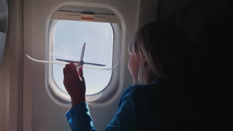 The-Girl-Is-Playing-With-A-Small-Toy-Airplane-In-The-Cabin-Of-The-Airliner-Baby-Dreams-Concept-4k-Vi