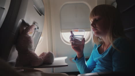 A-Girl-Drinks-Water-In-The-Cabin-Of-The-Plane-4k-Video