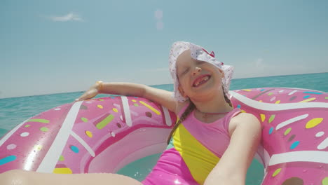 A-Little-Girl-In-A-Cool-Hat-And-A-Bright-Bikini-Is-Riding-On-A-Circle-And-Making-A-Selfie-Smiling-At