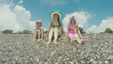 A-Young-Mother-In-A-Cool-Colorful-Hat-With-Two-Children-Sitting-On-The-Coast-Playing-Fun-With-The-Su