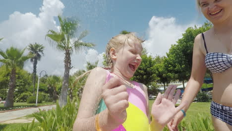 A-Young-Mother-With-Her-Little-Daughter-Is-Having-A-Fun-Shower-By-The-Pool-In-The-Seaside-Resort
