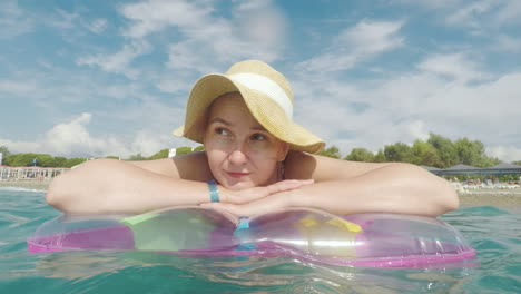 A-Young-Woman-In-A-Straw-Hat-Is-Floating-On-An-Inflatable-Mattress-On-The-Seashore-Beach-Vacation
