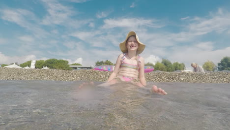 A-Cool-Girl-In-A-Pink-Bathing-Suit-And-Wearing-A-Broad-Brimmed-Hat-Is-Having-Fun-On-The-Seaside-Play