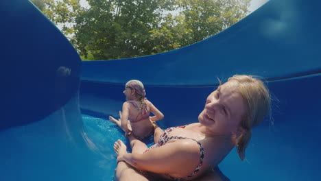 A-Happy-Family-With-A-Child-Is-Riding-A-Water-Slide-Laughing-Waving-Their-Hands-At-The-Camera-Slow-M