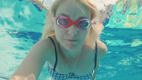 A-Young-Woman-Shoots-Herself-In-The-Video-Under-The-Water-Floats-In-The-Pool-Looks-Into-The-Camera-W