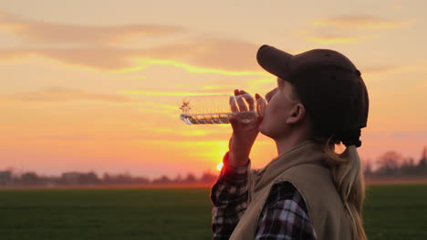 Tired-Farmer-Woman-Drinking-Clean-Water-From-Bottle-At-Sunset