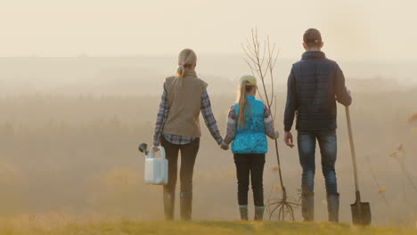 Family-With-A-Tree-Seedling-A-Sprinkler-And-A-Shovel-Standing-In-A-Picturesque-Place