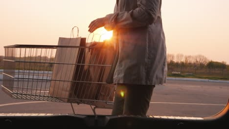 Woman-s-Silhouette-Opens-The-Trunk-Of-A-Car-Puts-There-Paper-Shopping-Bags