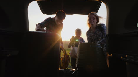 The-Family-With-The-Child-Is-Going-On-A-Trip-Together-They-Put-The-Bags-In-The-Trunk-Of-The-Carr