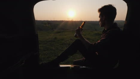 A-Teenager-Sits-In-The-Trunk-Of-A-Car-And-Drinks-Beer-From-A-Bottle