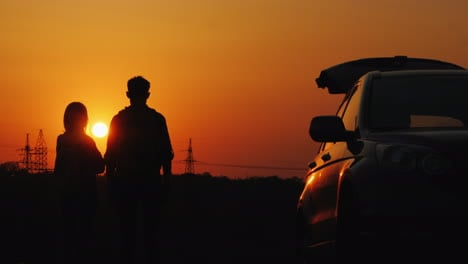 A-Young-Couple-Is-Standing-Near-His-Car-And-Admiring-The-Sunset-Over-The-Guesthouse