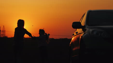 A-Woman-And-Her-Daughter-Arrived-By-Car-In-A-Picturesque-Place-Rejoice-And-Admire-The-Sunset
