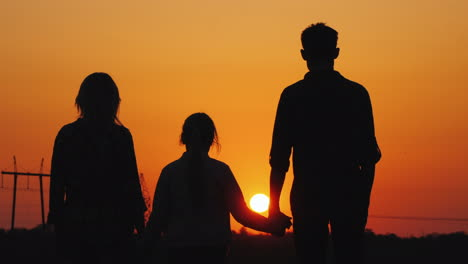 Family-Of-Three-Admiring-The-Orange-Sunset-Over-The-City-Rear-View