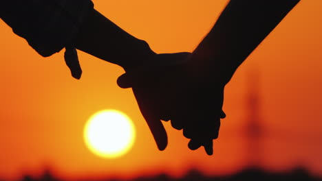 Young-Couple-Holding-Hands-On-The-Background-Of-A-Large-Setting-Sun
