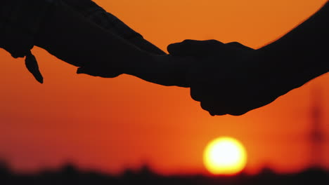 Man-And-Woman-Holding-Hands-Against-The-Sunset-And-Red-Sky