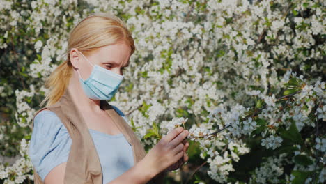 A-Woman-In-A-Gauze-Bandage-Examines-A-Flower-Against-A-Blossoming-Tree-Allergic-Disease-Problems