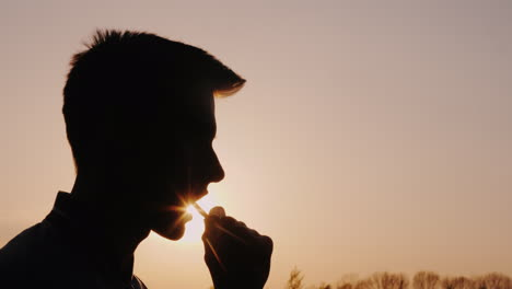 Profile-Of-A-Teenager-Eating-Snacks-Silhouette-Against-The-Setting-Sun
