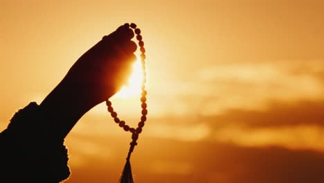 Hand-Holds-Rosary-Against-The-Sky-And-The-Setting-Sun-Sincere-Prayer-And-Meditation