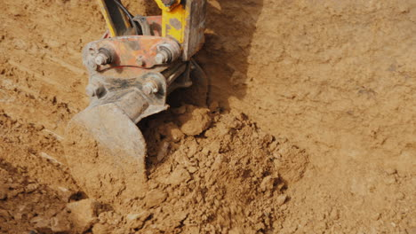 Powerful-Excavator-Bucket-Extracts-Ground-From-The-Pit-Laying-Communication-At-The-Construction-Site