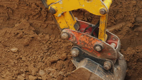 Earthmoving-Equipment-At-A-Construction-Site-Excavator-Bucket-Removes-Ground-From-Trench