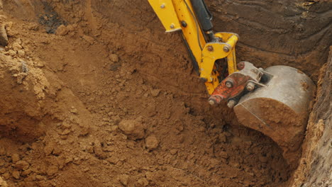 Excavator-Bucket-Extracts-Ground-From-Trench-Excavation-Work-At-The-Construction-Site