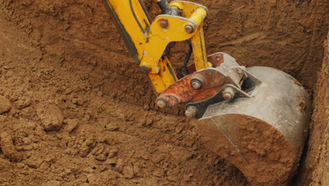 A-Large-Excavator-Bucket-Extracts-Soil-From-The-Pit-Excavation-Work-At-A-Construction-Site