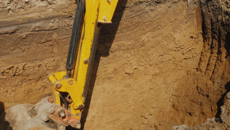 Excavator-Bucket-Extracts-Ground-From-Deep-Trench