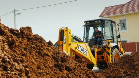Excavator-Digs-A-Hole-For-Laying-Communications-Against-The-Background-Of-A-Modern-Two-Story-House