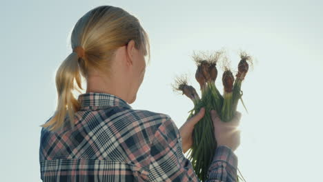 Back-View-Of-A-Female-Farmer-With-A-Green-Onion-In-Her-Hands-Organic-Farming-Concept