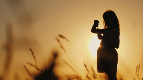Silhouette-Of-A-Girl-Playing-With-Soap-Bubbles-In-The-Tall-Grass-At-Sunset