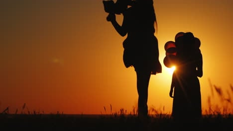 A-Child-Runs-To-His-Mom-Against-The-Backdrop-Of-A-Beautiful-Landscape-At-Sunset