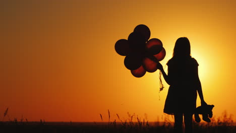 A-Child-With-Balloons-And-A-Teddy-Bear-In-His-Hand-Is-Standing-At-Sunset-Farewell-To-Childhood-Conce