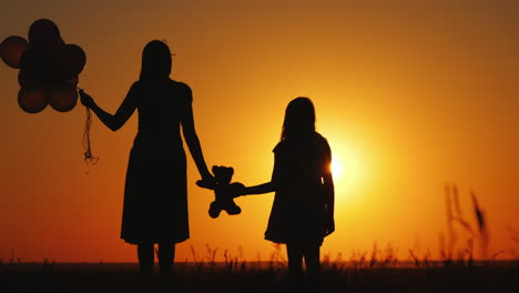 Middle-Aged-Woman-With-Her-Daughter-Admiring-The-Sunset-Holding-A-Teddy-Bear-Together