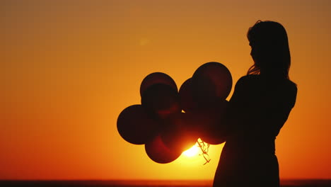 Silhouette-Of-A-Woman-With-Balloons-At-Sunset-Nostalgia-Concept