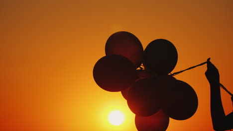 A-Hand-Holds-Several-Balloons-At-Sunset