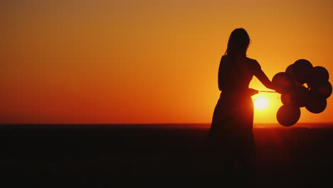 Silhouette-Of-A-Woman-Carelessly-Spinning-With-Balloons-In-Her-Hand-At-Sunset