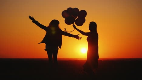 Mom-And-Daughter-Are-Having-Fun-At-Sunset-Dancing-And-Holding-Balloons