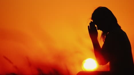 Silhouette-Of-A-Woman-Praying-Against-The-Background-Of-An-Orange-Sky-And-A-Large-Setting-Sun