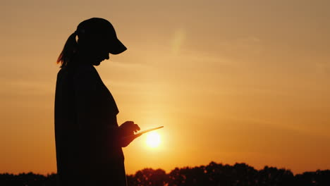 Silhouette-Of-A-Woman-Farmer-Working-With-A-Tablet-At-Sunset-Side-View