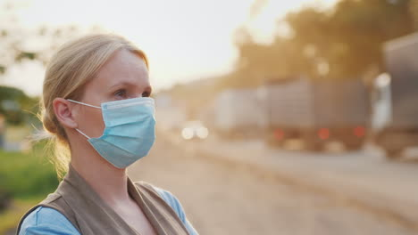 A-Woman-In-A-Protective-Mask-On-A-Dusty-Road-Ecology-Problems-Concept